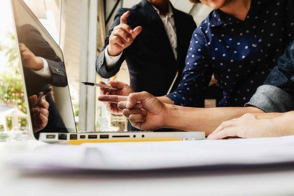 des gens pointent leurs stylos vers un ordinateurs